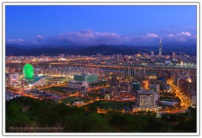 遠方的 Taipei 101、山腳的美麗華摩天輪、麥帥一橋、麥帥二橋,開始替城市點亮色彩。大直的街道與中間的松山機場的飛機,也開始忙碌起來。