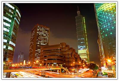 信義計畫區,一個眾多企業總部進駐同時具有希望,夢想與幻境的台北的「曼哈頓」,昨日的的國貿大樓、展覽大樓、國際會議中心及凱悅大飯店與今日的震旦企業,加上明日的台北 101,在夜色裡相互輝映。